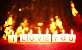 Bougies avec imprimé signe que je t'aime, le flou fond de lumières — Photo