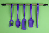 Plastic kitchen utensils on silver hooks on green background — Stock Photo