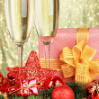 Glasses of champagne with gift box on shiny background — Stock Photo
