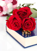 Wedding rings with roses on bible isolated on white — Stock Photo
