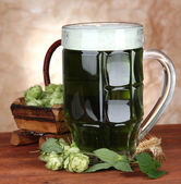 Glass of green beer and hops, on wooden table — Stock Photo