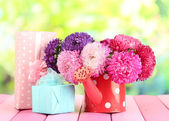 Gifts and flowers in watering can, on nature background — Stock Photo