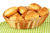 Saborosos croissants na cesta de vime na mesa no fundo branco — Foto Stock