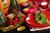 Table setting for Halloween with pumpkin and candles close-up — Stockfoto