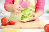 Mulher sorridente feliz em preparar sanduíche de cozinha, close-up — Foto Stock