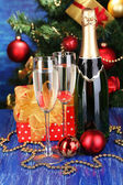 Bottle of champagne with glasses and Christmas balls on wooden table on Christmas tree background — Stok fotoğraf