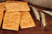 Delicious crackers with spikes on wooden table on sackcloth background — Stock Photo