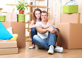 Young couple sitting in new house on staircase background — Stock Photo
