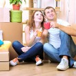 Young couple celebrating moving to new home — Stock Photo #33951517