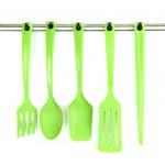 Plastic kitchen utensils on silver hooks isolated on white — Stock Photo