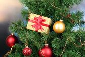 Dárek na vánoční stromeček na pozadí místnosti — Stock fotografie