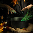 Witch in scary Halloween laboratory on dark color background — Stock Photo #34101255