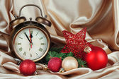 Alarm clock with Christmas decoration on golden cloth background — Stock Photo