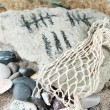 Counting days by drawing sticks on stone with stones and shells on sand background — Stock Photo