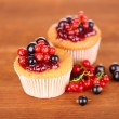 Tasty muffins with berries on wooden background — Stock Photo #34112051