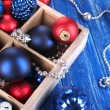 Christmas toys in box on wooden table close-up — Stock Photo #34112141