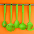 Plastic kitchen utensils on silver hooks on orange background — Stock Photo #34112663