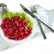 Stock Photo: Beet salad on plate on napkin on wooden board isolated on white