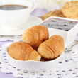 Tasty croissants and cup of coffee on table close-up — Stock Photo #34113569