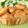 Tasty croissants in wicker basket on table on white background — Stock Photo #34113631