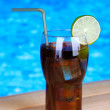 Tasty cocktail on swimming pool background — Stock Photo #34114099