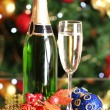 Bottle of champagne with glass and Christmas balls on Christmas tree background — Stock Photo