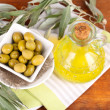Olives in bowl and oil with branch on napkin on wooden board on table — Foto Stock