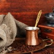 Coffee grinder, turk and coffee beans on golden tray on wooden background — Stock Photo