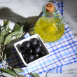 Olives in bowl with branch on sackcloth on wooden board on table — Foto Stock