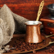 Coffee grinder, turk and coffee beans on golden tray on wooden background — Foto Stock