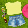 Top, shorts and beach items on bright green background — Stock Photo #34115679