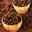 Coffee beans in bowls on wooden background — Stock Photo