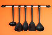 Plastic kitchen utensils on silver hooks on orange background — Stock Photo