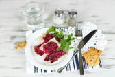 Beet salad on toasts on plates on wooden table — Stock Photo