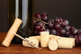 Wine and corks on wooden table on brown background — Stock Photo