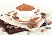 Cocoa powder in cup on napkin on wooden table — Stockfoto