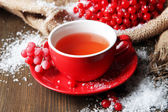 Still life with viburnum tea in cup, berries and snow, on sackcloth napkin, on wooden background — Stock Photo