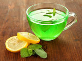 Transparent cup of green tea with lemon and mint on wooden background — Stock Photo