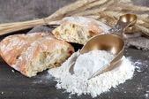 The wholemeal flour in scoop on wooden table on sackcloth background — Stock Photo