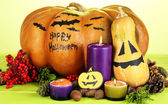 Composition for Halloween with pumpkins and candles on wooden table on color background — Стоковое фото