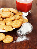 Delicious crackers with salt and tomato juice on wooden background — 图库照片