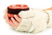 Cup with knitted thing on it in female hands isolated on white — Stock Photo