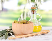 Olive oil and olives in bowl on napkin on wooden table on nature background — Stock Photo