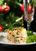 Russian traditional salad Olivier, on wooden table, on bright background — Stok fotoğraf