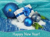 Composición con bolas de navidad, caja de regalo y nieve sobre fondo de madera color — Foto de Stock
