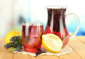 Rotes basilikum limonade im krug und glas, auf holztisch, auf hellem hintergrund — Stockfoto