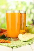Glasses of juice, apples and carrots on white wooden table, on green background — Stock Photo
