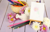 Composition of flowers and  easel with picture — Stock Photo