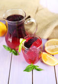 Red basil lemonade in jug and glass, on wooden table background — Foto Stock