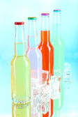 İçecekler buz üzerinde mavi arka plan ile cam şişelerde — Stok fotoğraf